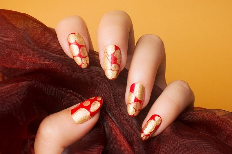 Artsy Red Nails With Gold Flakes