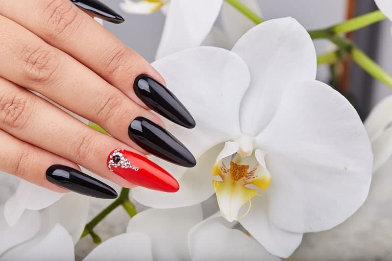 Long Oval Nails In Black Red Polish With A Gemstone Design